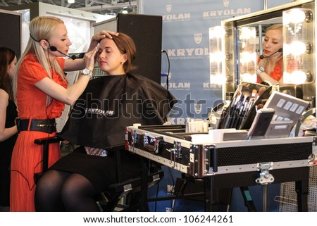MOSCOW-APRIL 19: Visagist doing makeup at the international exhibition of professional cosmetics and beauty salon equipment INTERCHARM on April 19, 2012 in Moscow - stock photo