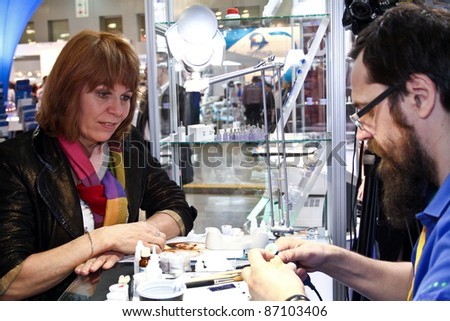 MOSCOW - APRIL 27: Woman looks at dental technician working at the international exhibition of the dental professionals and industry on April 27, 2011 in Moscow - stock photo