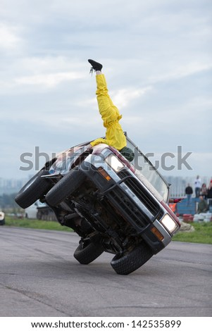 MOSCOW - AUG 25: Stuntman stands upside down on car traveling on two wheels on Festival of art and film stunt Prometheus in Tushino, Aug 25, 2012 in Moscow, Russia. The festival was organized in 1998. - stock photo