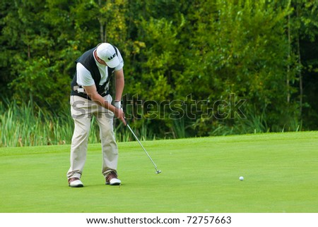 MOSCOW - AUGUST 8: An unidentified golfer finishes his swing at the annual VI Moscow Festival Retrostyle event for fans and professionals at the Le Meridien Moscow County Club on August 8, 2008 in Moscow, Russia - stock photo