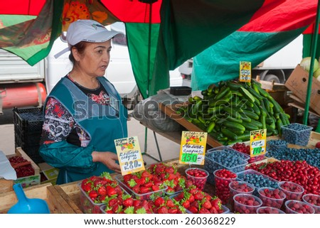 MOSCOW - AUGUST 08: The saleswoman selling berries in Vegetable Fair on Leskov Street on August 8, 2014 in Moscow. - stock photo