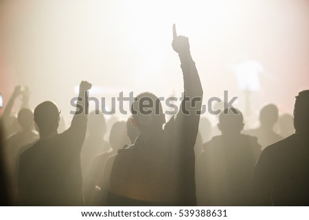 MOSCOW - 18 DECEMBER,2016: Famous rapper big concert in night club.Music fans on crowded dance floor wave with hands above their head. Cool nightclub party,people enjoy the music.Performing arts event