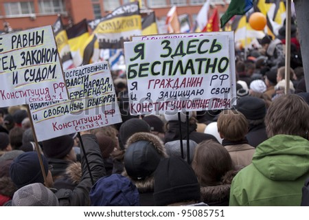 "MOSCOW - DECEMBER 24: Protestors with posters with inscription: ""I am here for free!"". Protest against election results. December 24, 2011 in Moscow, Russia. - stock photo"