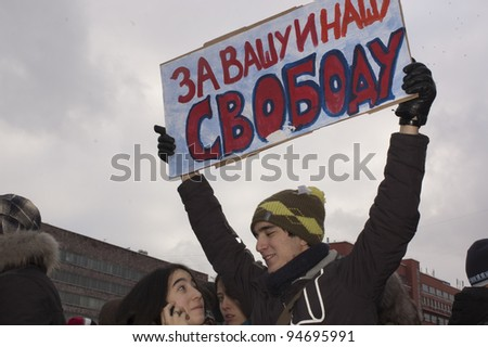 "MOSCOW - DECEMBER 24: Young man, holding a poster with inscription: ""For yours and our Freedom"". Protest against election results. December 24, 2011 in Moscow, Russia. - stock photo"