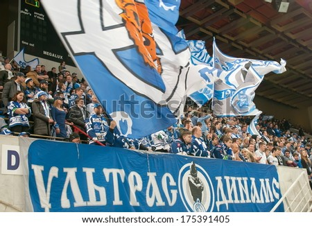 MOSCOW - JANUARY 28, 2014: Unrecognized fans of the club Dynamo during the KHL regular Hockey match Dynamo (Moscow) - Slovan (Bratislava) in sports palace Luzhniki. Final score 2:3 - stock photo