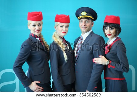 MOSCOW - JUL 09, 2015: Portrait of a crew of three beautiful flight attendants in red hat and one steward at DME RUNVAY in Domodedovo - stock photo