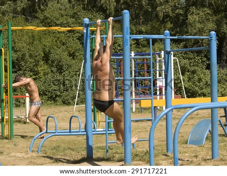 MOSCOW - JULY 20, 2014: people do physical exercises on beach in Serebryany bor (Silver forest) on Moskva-river, one of the most popular beaches of the city. - stock photo