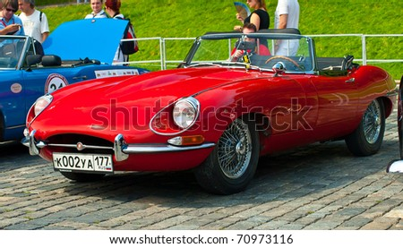 """MOSCOW -JULY 10: Red Jaguar E-Type. Modelyear 1963 on display at the start annual Rally of classical cars  """"Zolotoe kol'co"""" on Red Square on July 10, 2010 in Moscow, Russia - stock photo"""