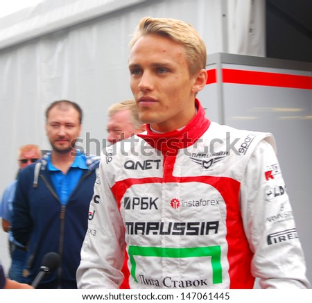 MOSCOW - JULY 20: Sportsman Max Chilton (Marussia F1 team) at Moscow City Racing. Formula 1 teams show in historical city center of Moscow. Taken on July 20, 2013 in Moscow, Russia.  - stock photo