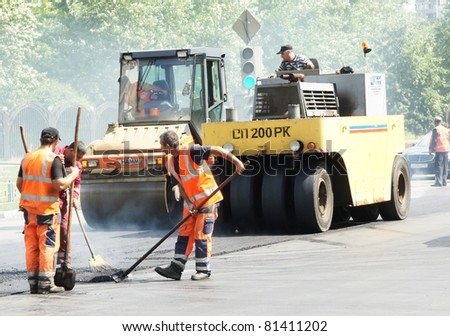 MOSCOW - JUNE 22: Brigade of workers repairs road under the program of planned repair in  Marino on June 22, In the government of Moscow have planned to repair in 2011 24,6 million in sq.m. of roads - stock photo