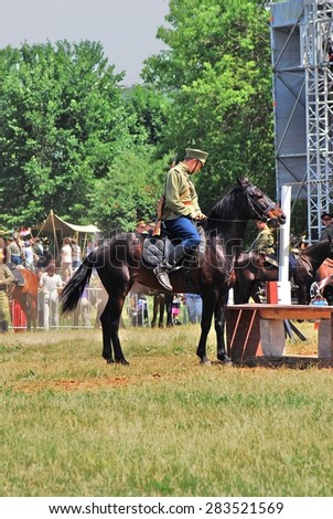 MOSCOW - JUNE 08, 2014: Horse riders competition. A rider is dressed in vintage military uniform. Times and Ages International Historical Festival in Kolomenskoye, Moscow.