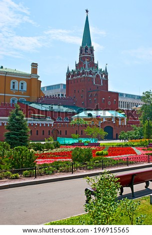 MOSCOW - JUNE 28, 2013: The Troitskaya Tower is the tallest one, it's the main visitors' entrance into the Kremlin, surrounded by flower beds of Alexander Garden, on June 28 in Moscow. - stock photo