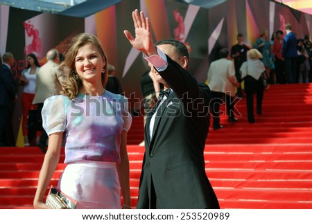 MOSCOW - JUNE 20, 2013: Tv presenter, actor Alexander Oleshko with a lady greets fans at XXXV Moscow International Film Festival red carpet opening ceremony. Taken on 20.06.2013 in Moscow, Russia. - stock photo