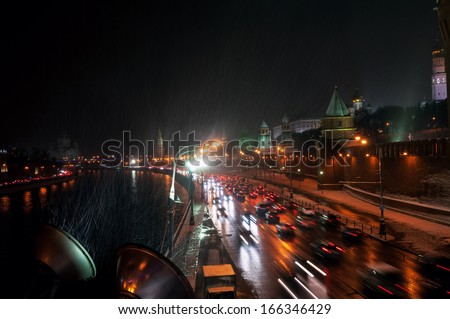 Moscow Kremlin wall and cars at the street at the snowstorm winter night