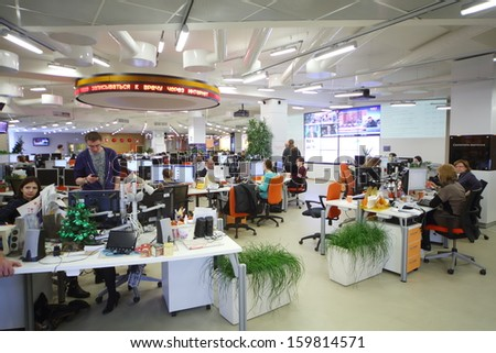 MOSCOW - MAR 5: Employees work in office buildings news agency RIA Novosti with green grass  and many screens on March 5, 2013 in Moscow, Russia. - stock photo