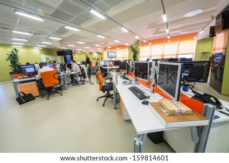 MOSCOW - MAR 5: Employees work in office buildings news agency RIA Novosti with plants and orange furniture on March 5, 2013 in Moscow, Russia. - stock photo