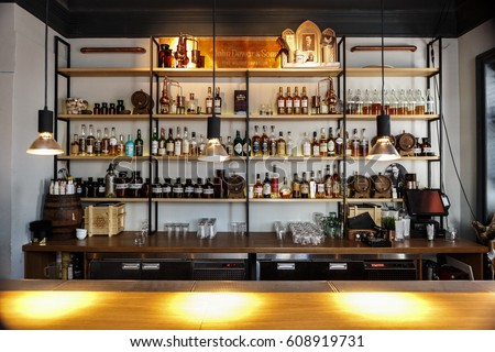 MOSCOW - 26 MARCH,2017: Illuminated Dewars bar stand with many alcohol drinks,variuous liquor beverages bottles.Bartender counter.Cognac,rum & cognac on background.Pub interior
