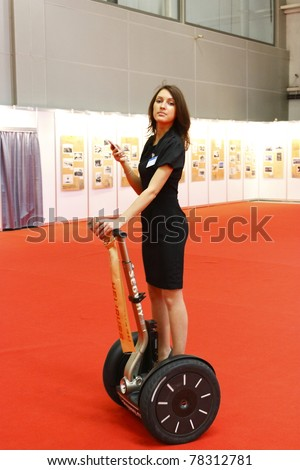"""MOSCOW- MAY 21: An unidentified woman rides a Segway during the """"4th International Exhibition of Helicopter Industry - HeliRussia-2011"""" on May 21, 2011 in Moscow - stock photo"""