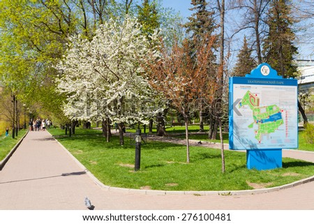 MOSCOW - MAY 07: Blooming apple tree and the map in Catherine Park on May 7, 2015 in Moscow. Catherine Park is located in Moscow's Meshchansky District. - stock photo