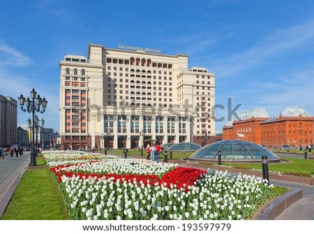 MOSCOW - MAY 12: Four Seasons Hotel Moscow building on Manezh Square on May 12, 2014 in Moscow. Tulips lawn is in the foreground. - stock photo