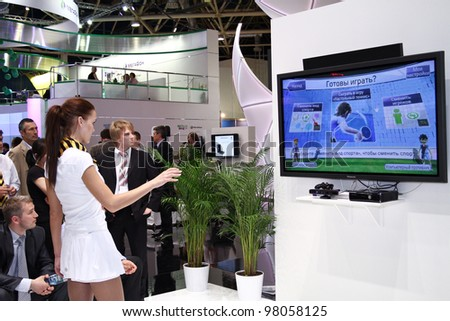 MOSCOW-MAY 11: Girl plays in videos tennis at the international exhibition of the telecommunications industry Sviaz-Expocomm on May 11, 2011 in Moscow - stock photo