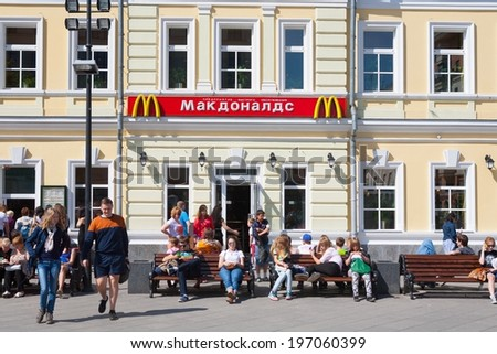 MOSCOW - MAY 31: People resting on benches near McDonald's restaurant building on Tolmachesvsky street on May 31, 2014 in Moscow.