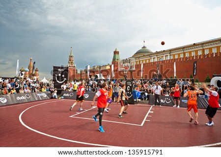 MOSCOW - MAY 27: People watch basketball game during Dudu Streetbasket fest on Red Square, May 27, 2012, Moscow, Russia. Dudu Streetbasket fest takes place within 8th sports forum GTO. - stock photo