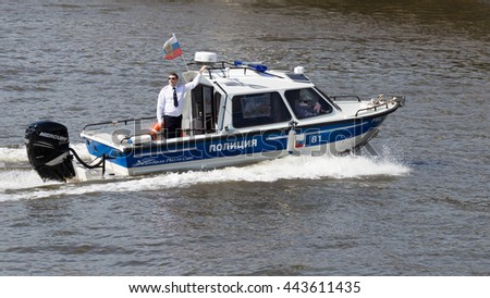 Moscow - May 9, 2016: Police Boat with the police, in black glasses, and on board the Russian flag patrol the territory of the Moscow River during the Victory parade on May 9th