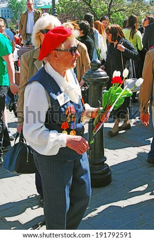 MOSCOW - MAY 09, 2014: Portrait of a war veteran woman holding flowers. Victory Day celebration in Moscow.