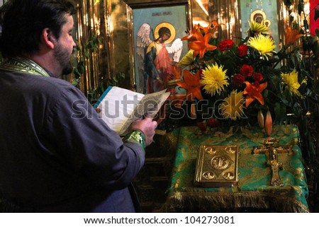 MOSCOW-MAY 3: Priest reads a prayer at the celebration of a Holy Trinity (Pentecost) by the church of St. Nicholas May 3, 2012 in Moscow