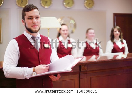 MOSCOW - MAY 22: Receptionist with folder at counter for guests in Bogorodino hotel, on May 22, 2013 in Moscow, Russia. Four-star Borodino hotel was built in 2007. - stock photo