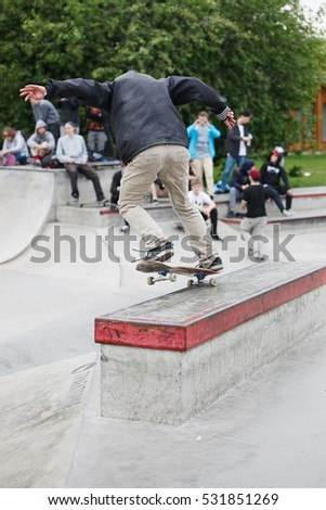 MOSCOW- 15 MAY,2016: Summer street skateboarding contest in outdoor skate park.Extreme skating in concrete skatepark.Skateboarder exercising.Extremal sport.Young skater boy grind nosegrind on ledge