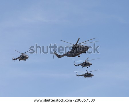 Moscow - May 7th, 2015: Mi-26 and Mi-8 formation flying against a blue sky 7, 2015, Moscow, Russia - stock photo