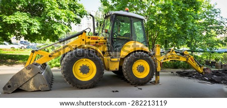 MOSCOW - MAY 26: The big yellow tractor digging asphalt on the street on May 26, 2015 in Moscow, Russia. - stock photo
