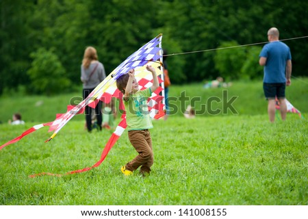 MOSCOW - MAY 25: Unidentified child flies kite at the kite festival in the park Tsaritsyno on May 25, 2013 in Moscow. - stock photo