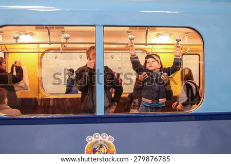 MOSCOW - MAY 5, 2015: Unidentified child opens a window in an old subway car at the exhibition of retro-cars dedicated to the 80th anniversary of the Moscow Metro. Public-event - stock photo