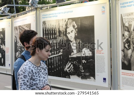 MOSCOW- MAY 13: Unidentified woman looking photo at the VDNH exhibition of war photos, on MAY, 2015 in Moscow. Public-event - stock photo