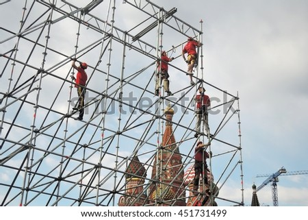 MOSCOW - MAY 01, 2016: Workers fixes holiday decoration on the Red Square in Moscow. They are dressed in red uniform. Saint Basils cathedral is seen at background.