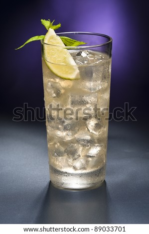 moscow mule cocktail with lemon garnish in front of a gold glitter background - stock photo