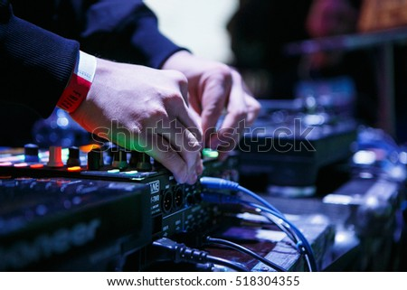 MOSCOW - 15 NOVEMBER,2016: DJ play music show on scene in nightclub.Club disc jockey mix tracks on sound mixing controller,pro audio equipment.Hands adjust trim regulator