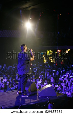 MOSCOW - 30 NOVEMBER,2016: Popular rap singer Jah Kalib sing on scene in night club.Big music show concert in nightclub.Bright stage lighting,crowded dancefloor.Rapper singing live.Entertainment event