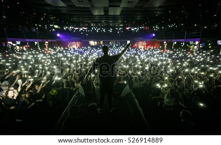 MOSCOW - 30 NOVEMBER,2016: Popular rap singer sing on scene in night club.Big music show concert in nightclub.Bright stage lighting,crowded dancefloor.Full club put thousand mobile phone lights on