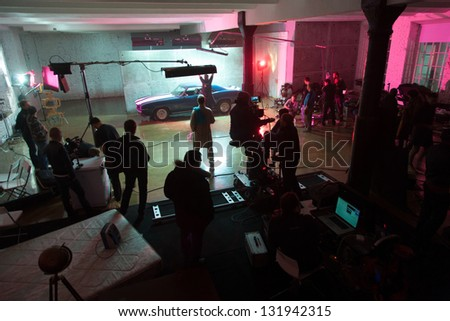 MOSCOW - OCT 23: Director, staff and actors on the set of the video singer Rene. Scene with the car on October 23, 2010 in White studio, Moscow, Russia. - stock photo