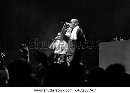 MOSCOW - 2 OCTOBER,2014: Big concert of famous Russian hip hop band Centr in nightclub.Young white rap singer guy singing in microphone on stage.Rapper doing the show on scene