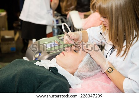 MOSCOW - OCTOBER 24: Cosmetologist applying permanent make up on eyebrows at the international exhibition of professional cosmetics and beauty salon equipment INTERCHARM on October 24, 2014 in Moscow - stock photo