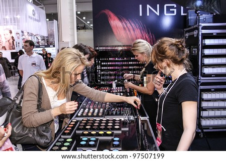 MOSCOW - OCTOBER 26: Girl chooses makeup at the international exhibition of professional cosmetics and beauty salon equipment INTERCHARM on October 26, 2011 in Moscow - stock photo