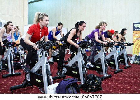 MOSCOW - OCTOBER 5: Group is training on a velosimulator at the international exhibition of the fitness and wellness industry, MIOFF on October 5, 2011 in Moscow - stock photo