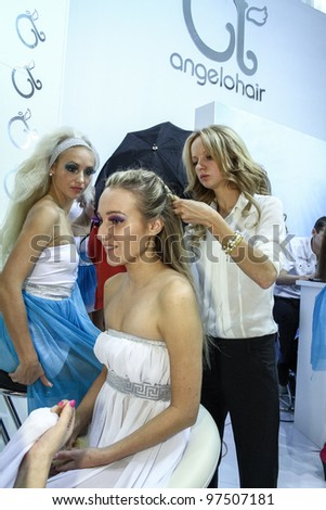 MOSCOW - OCTOBER 26: Hairdresser increases a client hair at the international exhibition of professional cosmetics and beauty salon equipment INTERCHARM on October 26, 2011 in Moscow