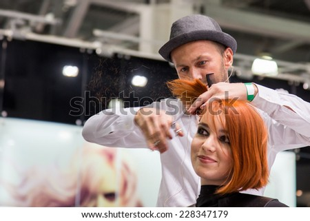 MOSCOW - OCTOBER 24: Hairstylist performs hair cut at the international exhibition of professional cosmetics and beauty salon equipment INTERCHARM on October 24, 2014 in Moscow - stock photo