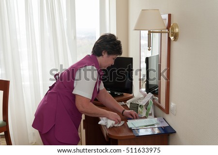 MOSCOW - OCTOBER 31: Maid woman, dressed in purple, arranging things on table at room in Izmaylovo hotel on October 31, 2016 in Moscow. Izmailovo is four-building hotel in Izmaylovo District of Moscow